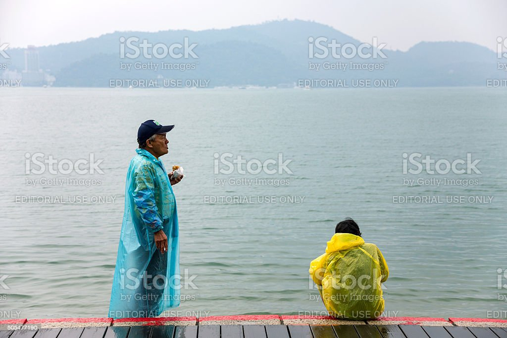 Old Taiwanese people by the lake eating stock photo