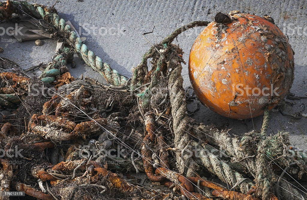 Old tangled fishing nets with orange sphere buoy royalty-free stock photo