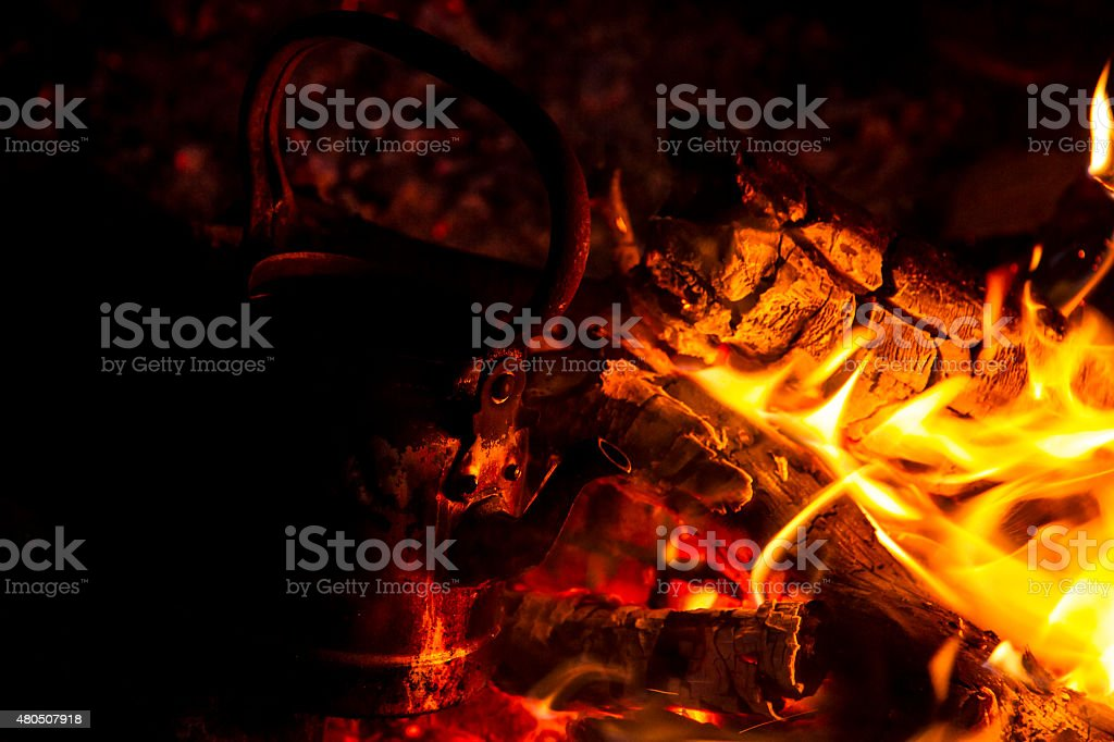 Old teapot boils on campfires stock photo