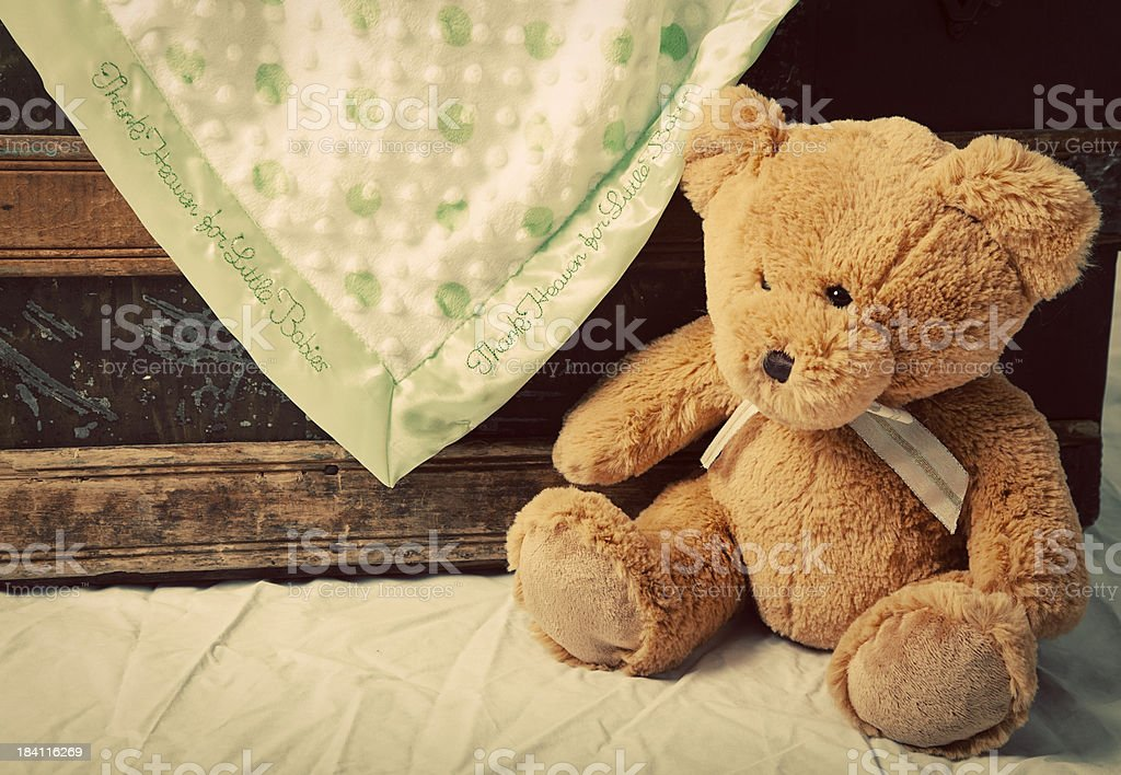 Old teddy bear near blanket-draped antique trunk stock photo