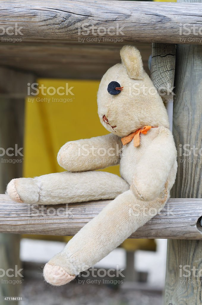old teddy bear on outdoor play equipment stock photo
