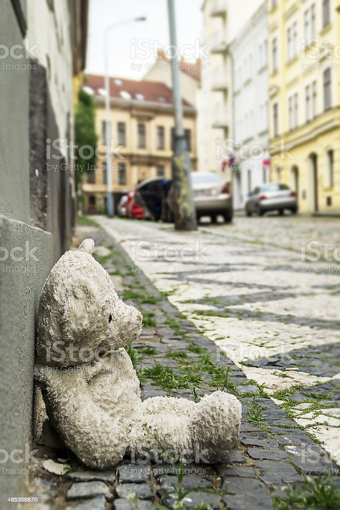 old teddy bear on the sidewalk in the city stock photo