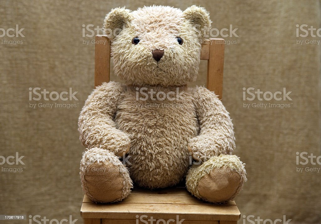 Old teddy bear sitting on wooden chair stock photo