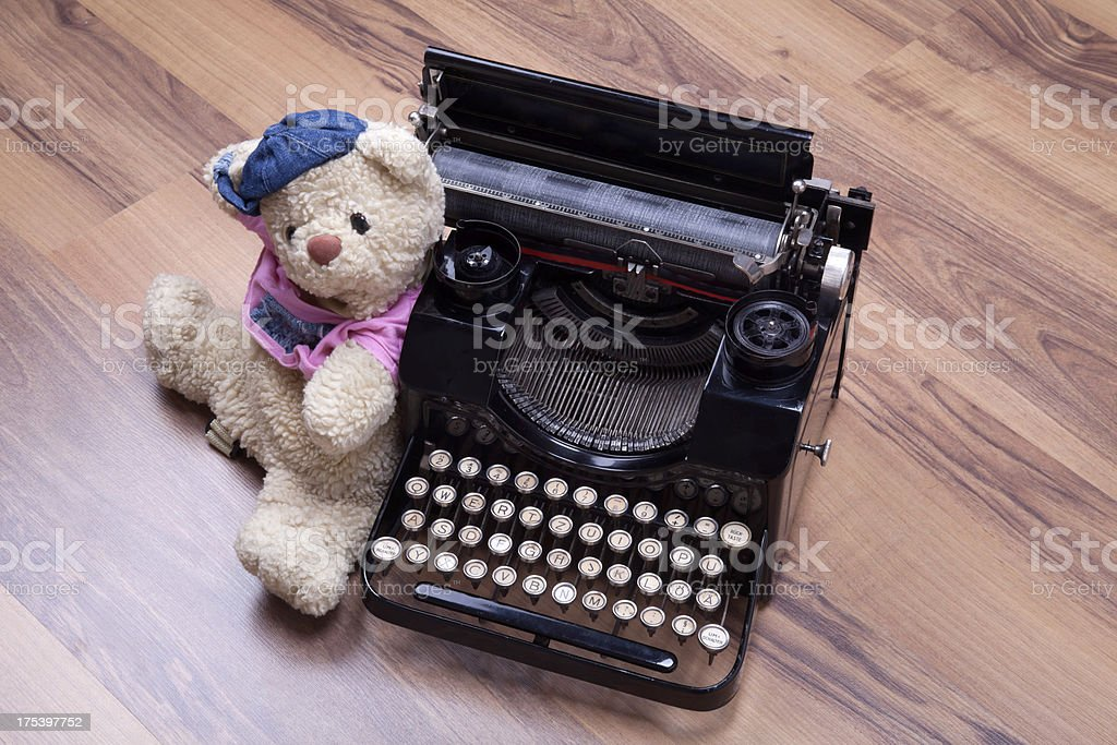 old teddy bear with type writer machine on wood background