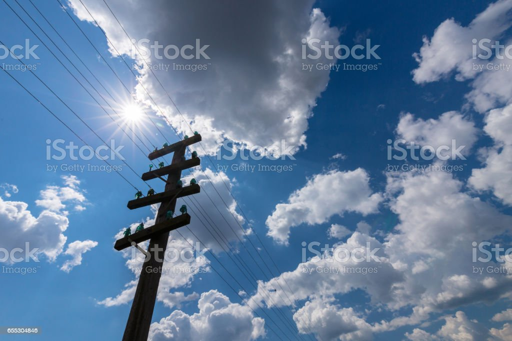 Old telegraph pole, profiled on sky with cumulus clouds, on a bright, sunny, day stock photo