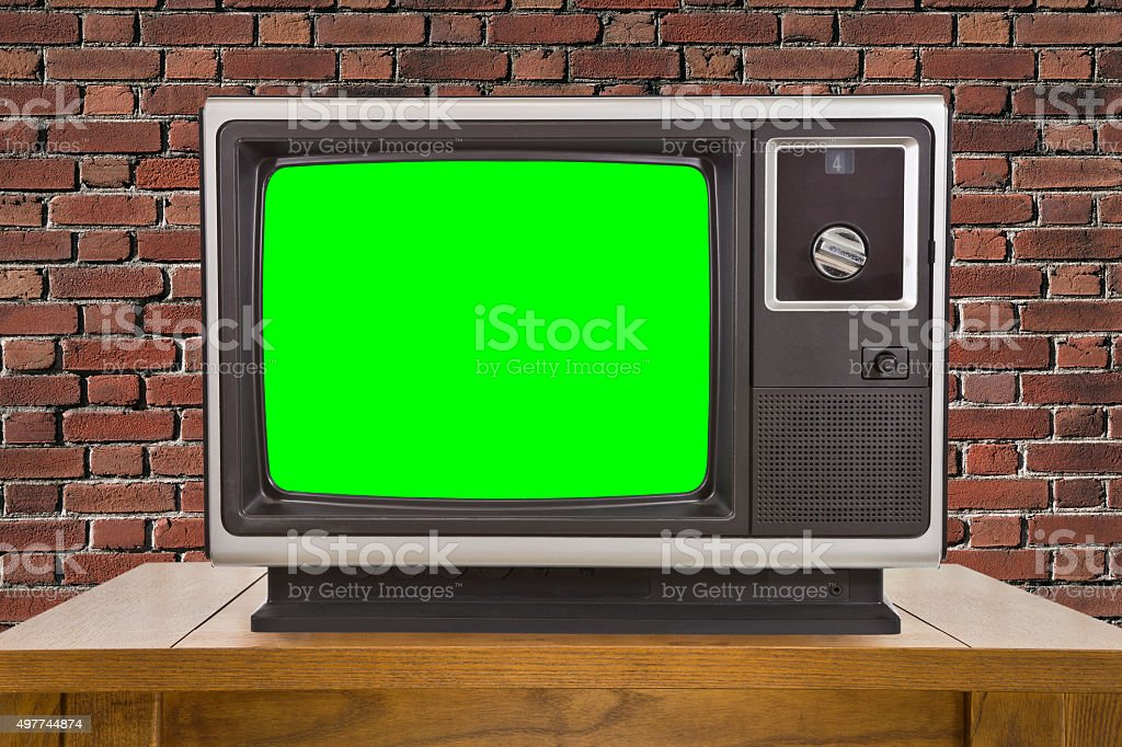 Old Television and Chroma Green Screen and Brick Wall stock photo