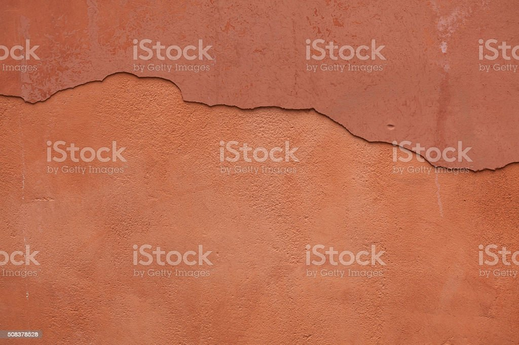 Old terracotta painted stucco wall with cracked plaster. Backgro stock photo