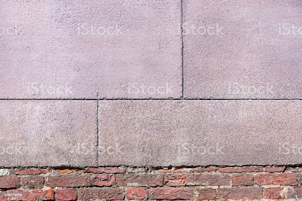 old texture of a brick wall with grained cement plaster stock photo