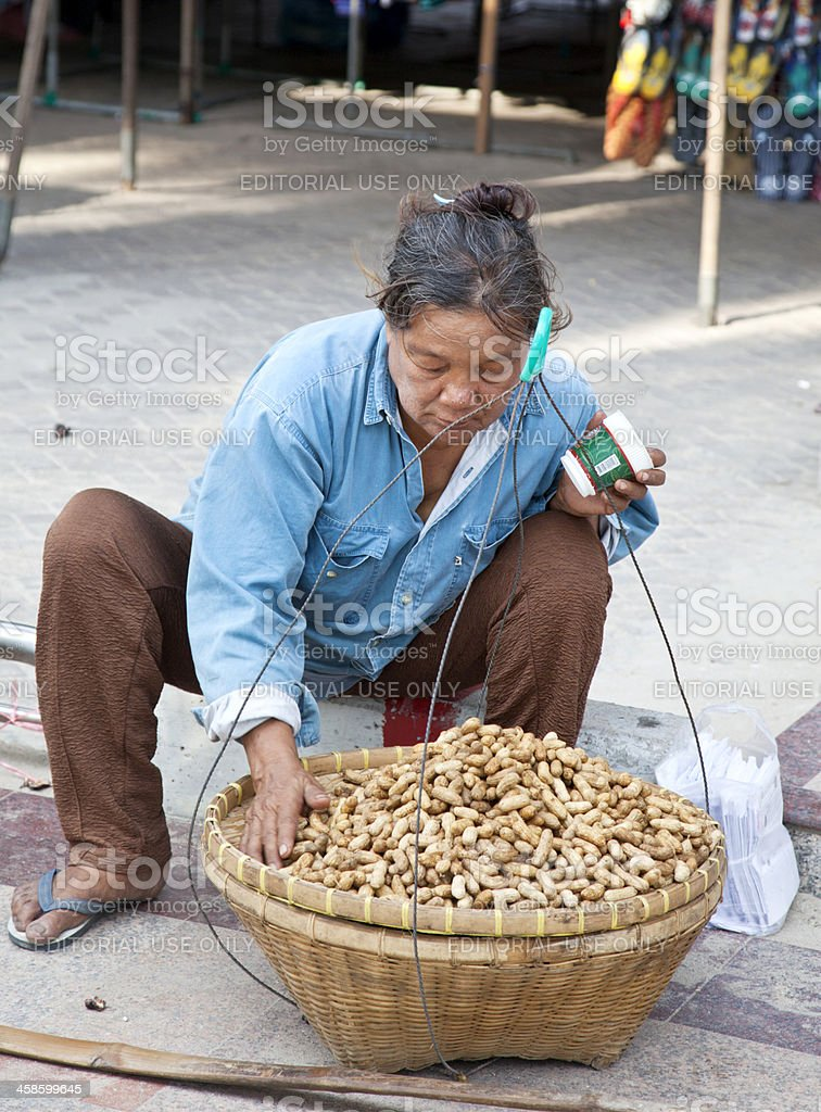 Old Thai woman arranging peanuts for sale stock photo