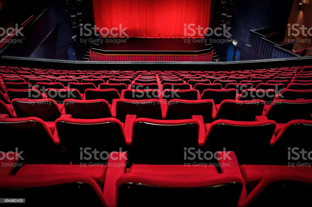 old theatre stage with rows of chairs in the foreground stock photo