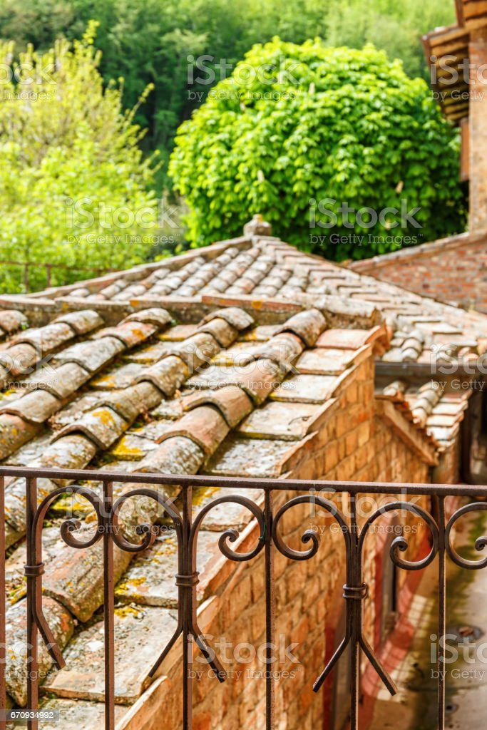 Old tile roof on a house with an ornate iron fence stock photo