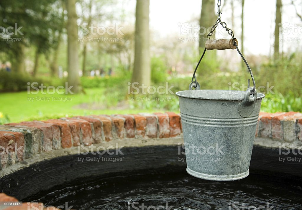 Old tin bucket hanging above well with trees in background stock photo