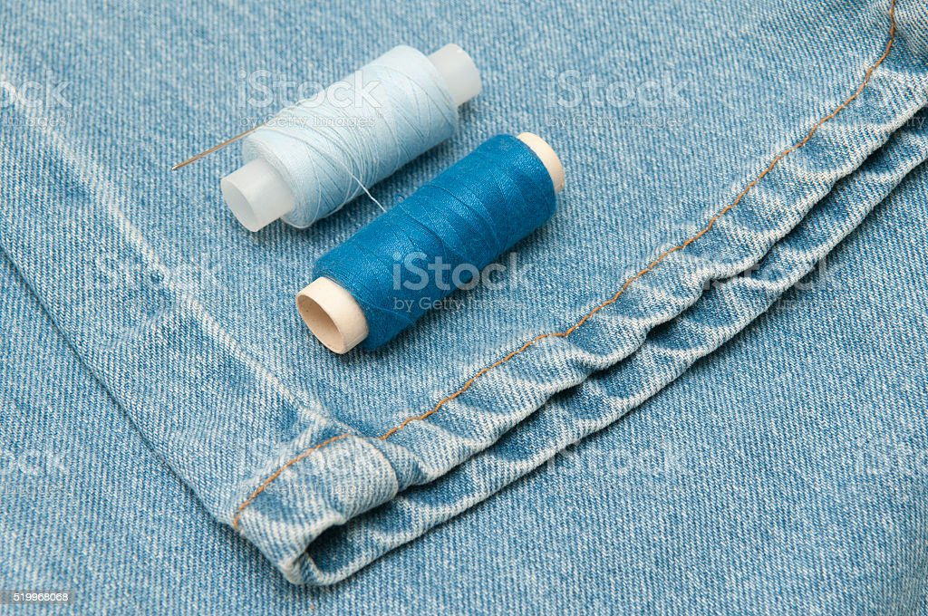 Old torn jeans on a background of burlap. stock photo