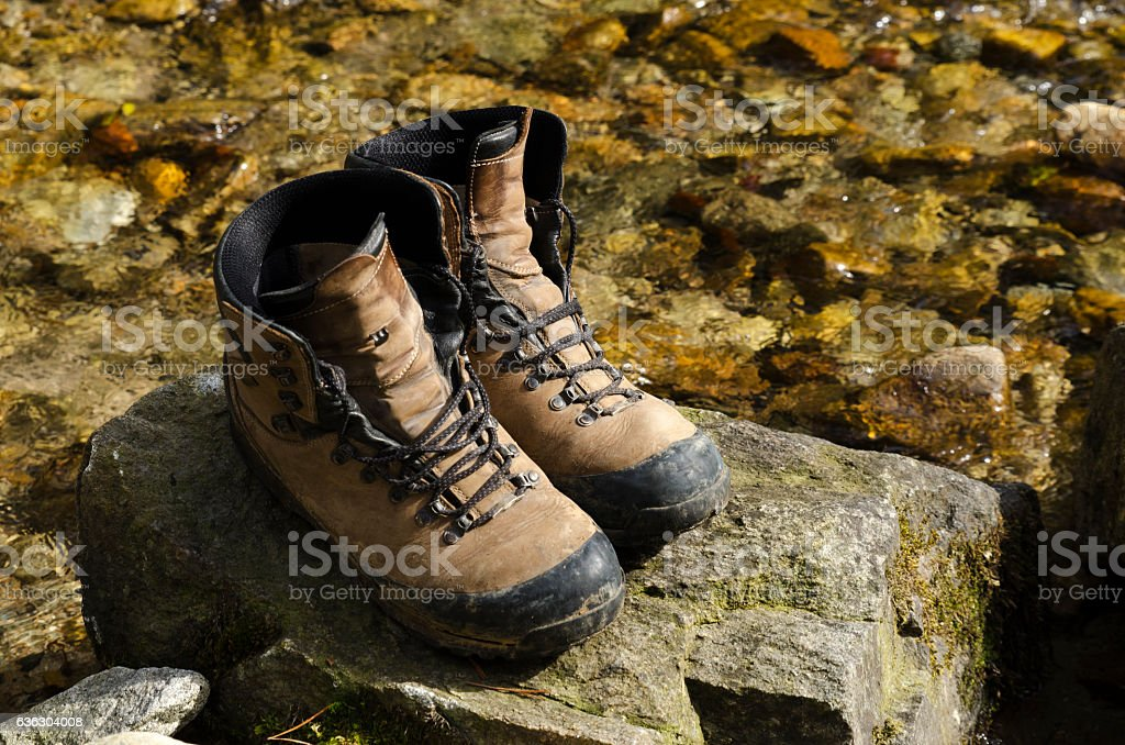 Old touristic shoes in a river stock photo