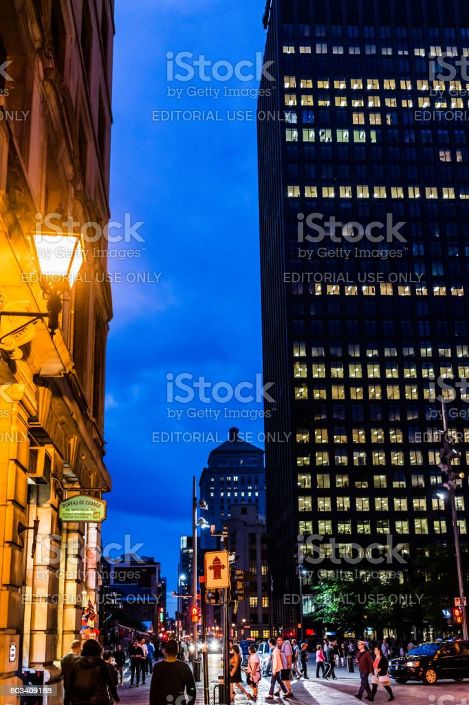Old town area with 500 Place D'Armes modern skyscraper building at night in evening outside in Quebec region city stock photo