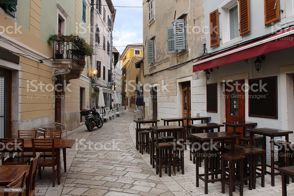 Old town street with restaurants  in Porec  in Croatia stock photo