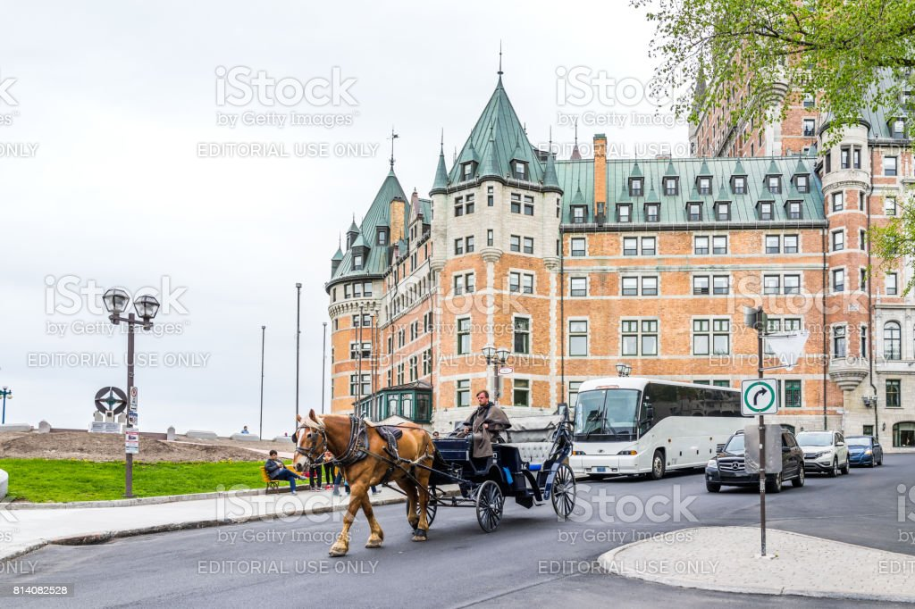 Old town street with view of hotel Chateau Frontenac, Champlain monument and horse buggy carriage stock photo