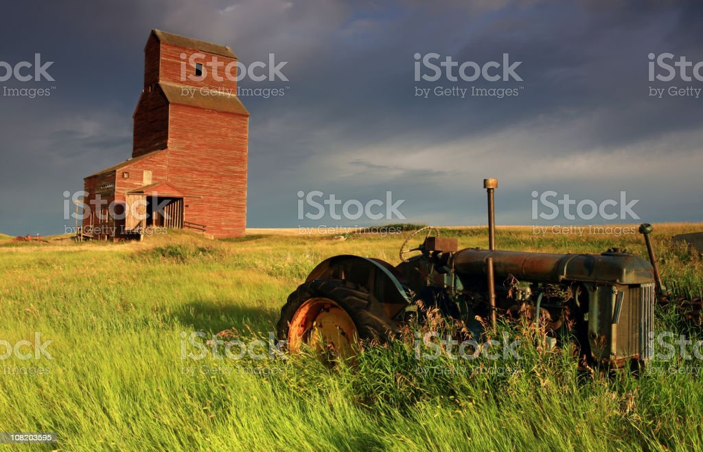 Old tractor and grain elevator on farm stock photo