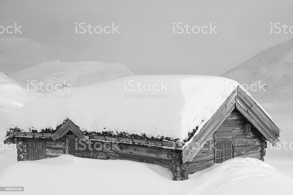 Old traditional Norwegian wooden log cabin house covered with snow royalty-free stock photo
