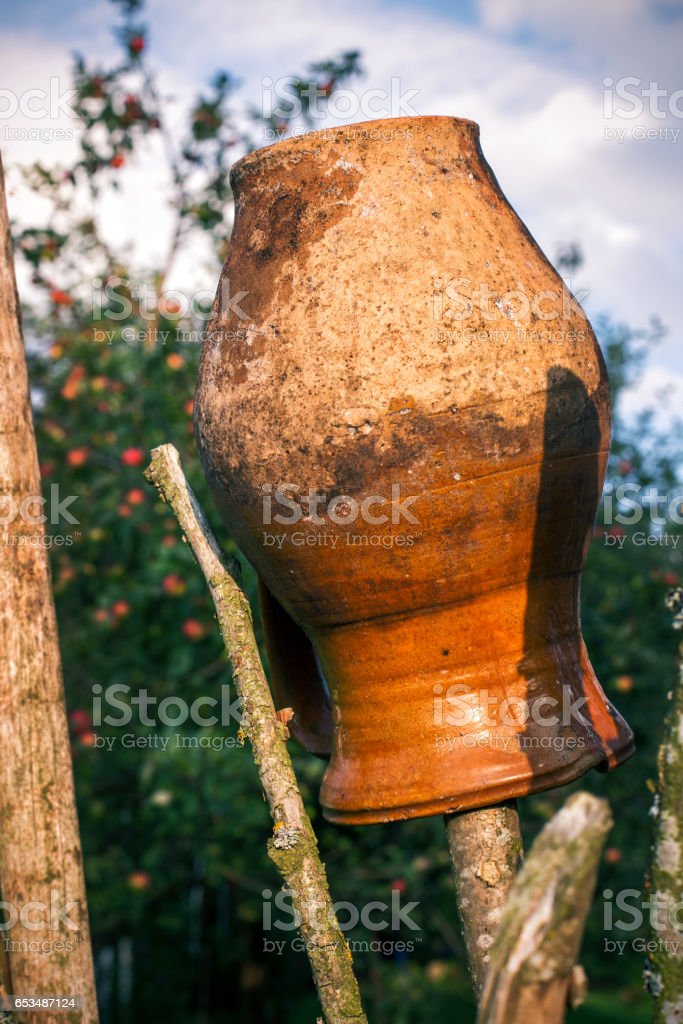 Old Traditional Ukrainian clay jug on the fence stock photo