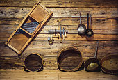 old traditional utensils hanging on wooden wall at kitchen