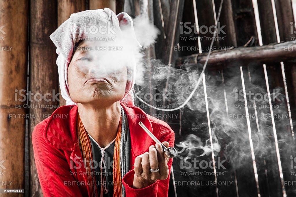 old tribal women wearing a traditional tribal sitting smoking stock photo