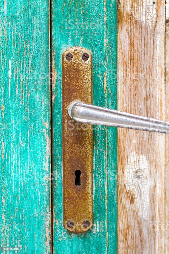 Old Turquoise-Green Wood Door with Rusty Handle (Detail) stock photo