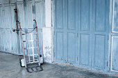 Old two wheel hand truck/cart and old wooden door background.