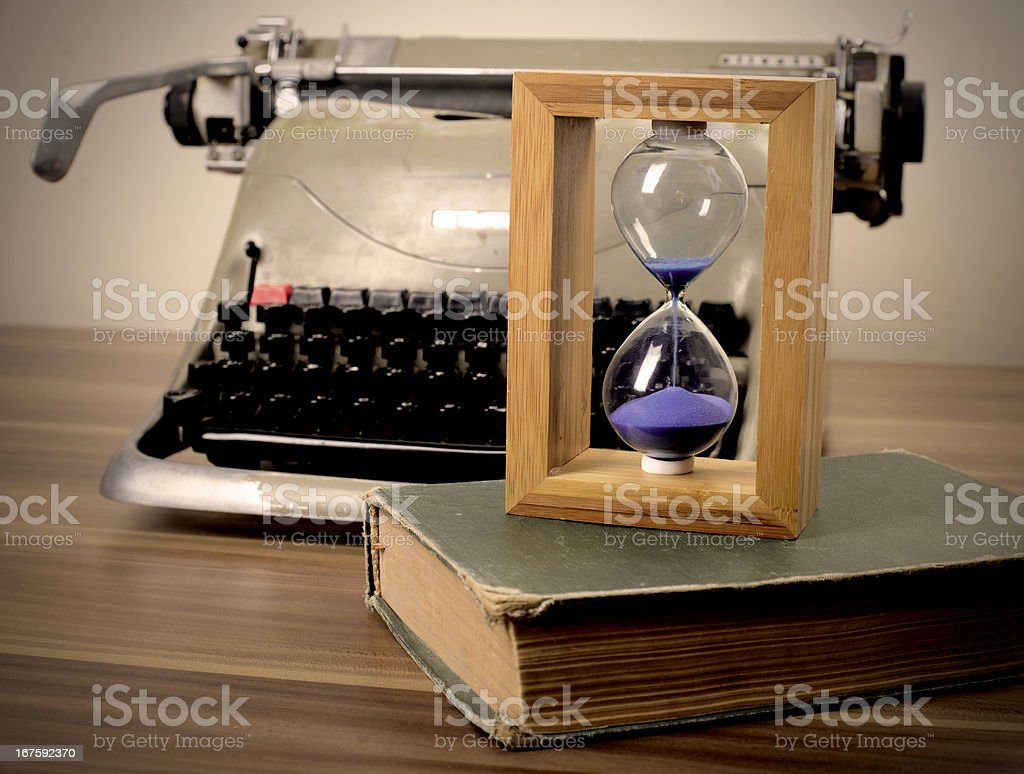 Old typewriter, book and hourglass royalty-free stock photo