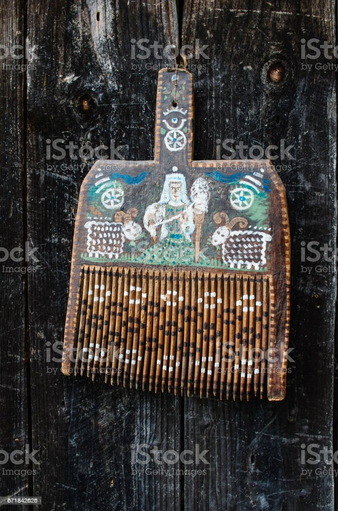 Old ukrainian traditional painted wooden wool comb hanging on dark timber background stock photo