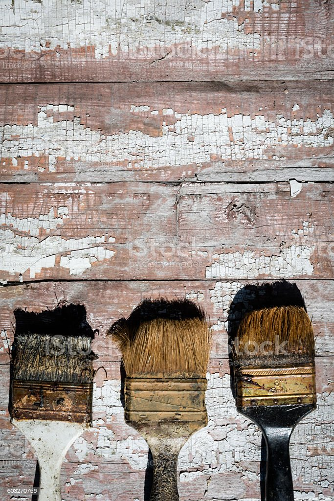 old used brushes against the background of an old paint stock photo