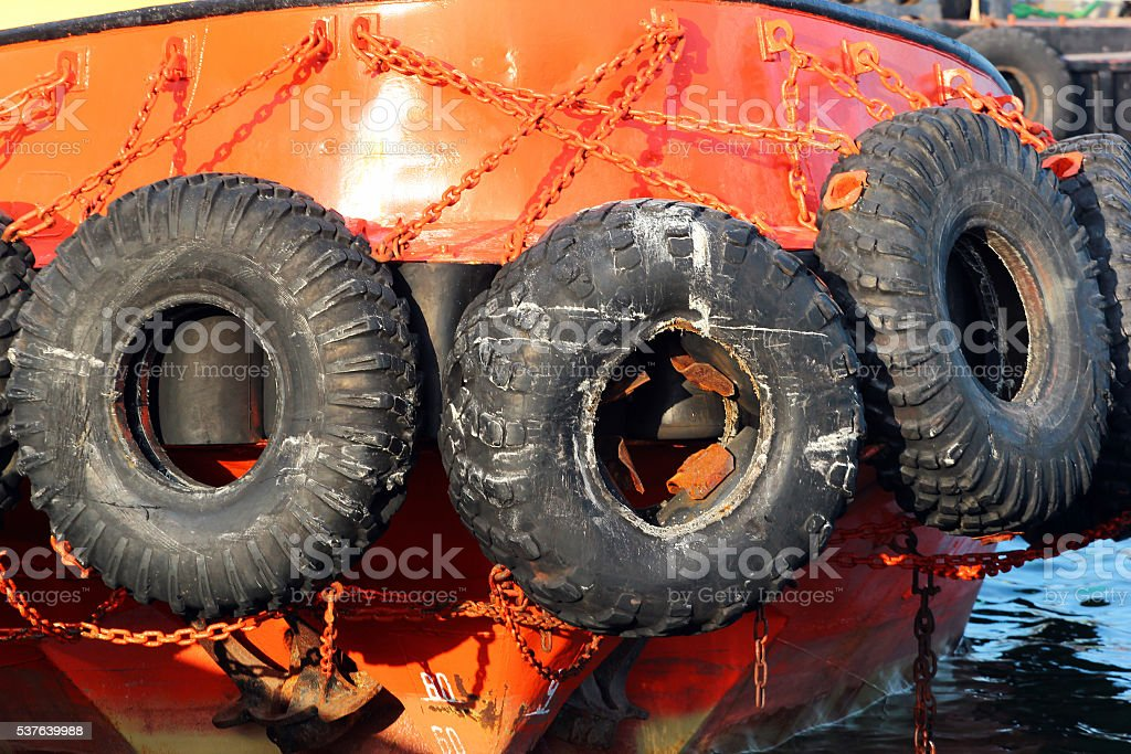 Old used car tires as fender on a shipboard stock photo