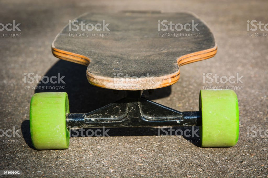Old used longboard on the ground. Black skateboard on an empty asphalt road. Shallow depth of field. Close up. stock photo