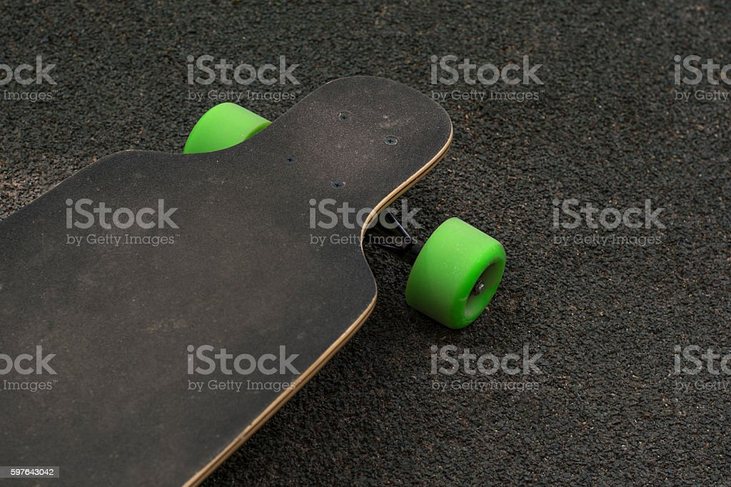 Old used skateboard isolated on the ground. stock photo