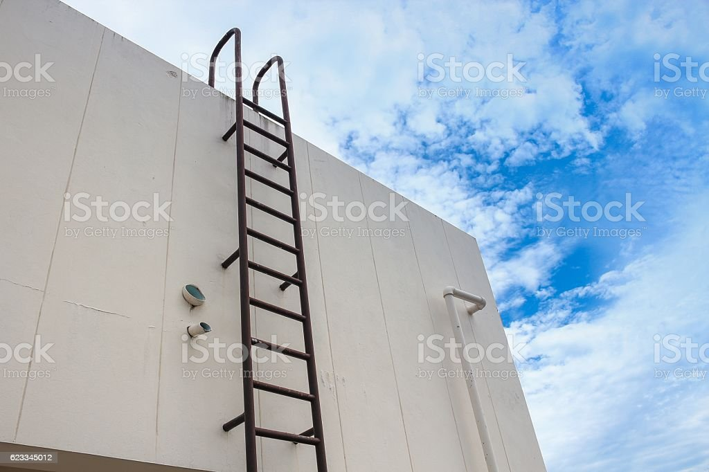 Old vertical industrial metal rusted ladder. Staircase to Water stock photo
