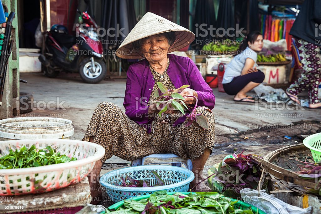 Old vietnamese woman at the street market, Vietnam stock photo