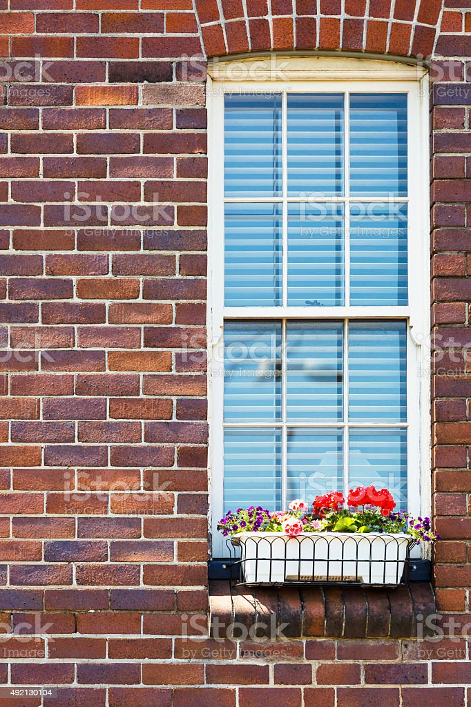 Old vindow with hanging basket full of flowers, brick building stock photo