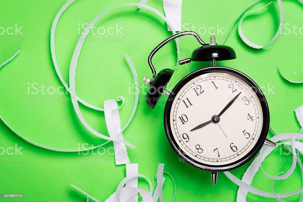 Old vintage alarm clock on the green surface stock photo