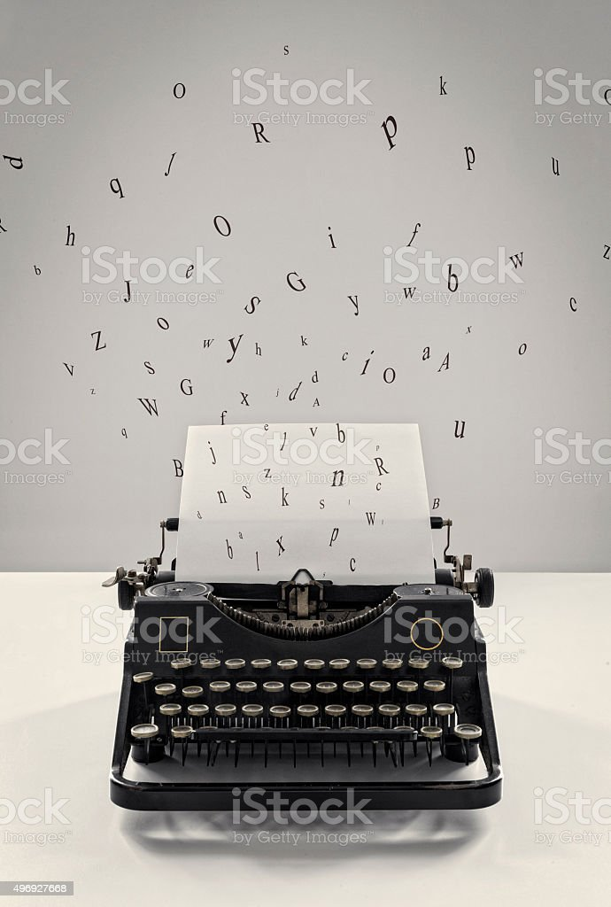 Old vintage black typewriter, flying letters, sheet of paper, creativity stock photo