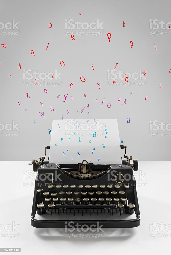 Old vintage black typewriter, multicolored flying letters, sheet of paper stock photo