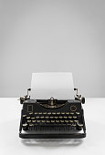 Old vintage black typewriter with empty sheet of paper