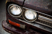 Old, vintage car headlight close-up. Shabby, rough antique transport