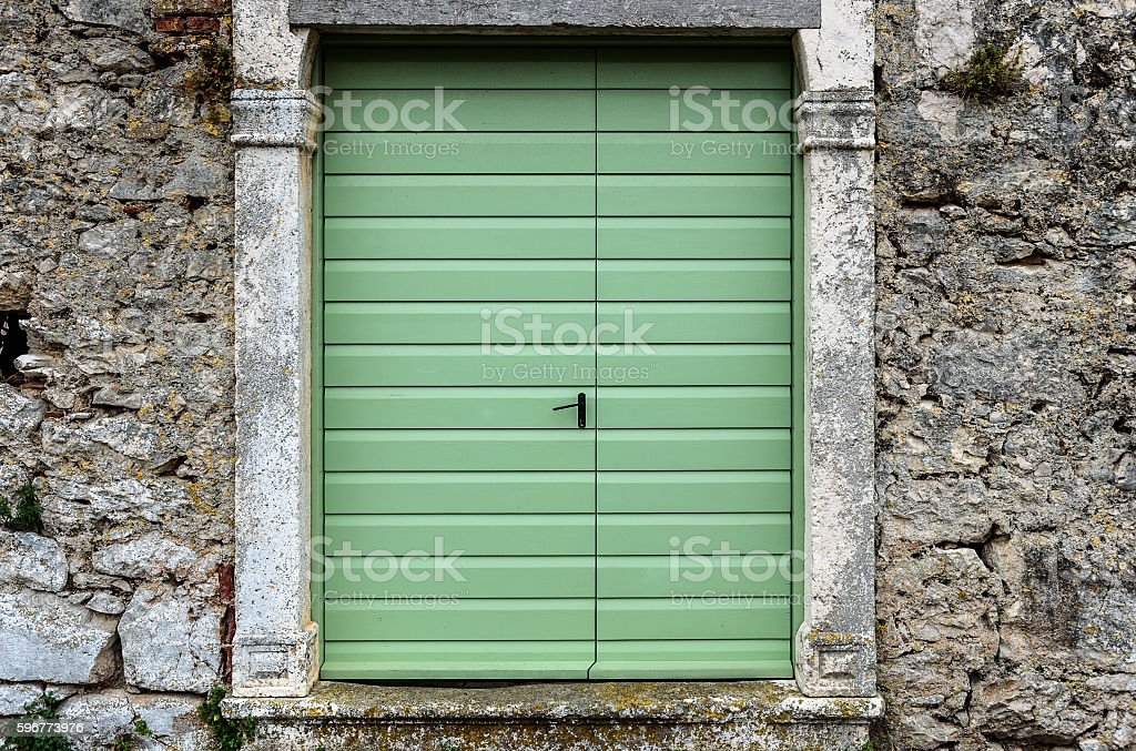 Old vintage green doors in a stone wall fence. stock photo