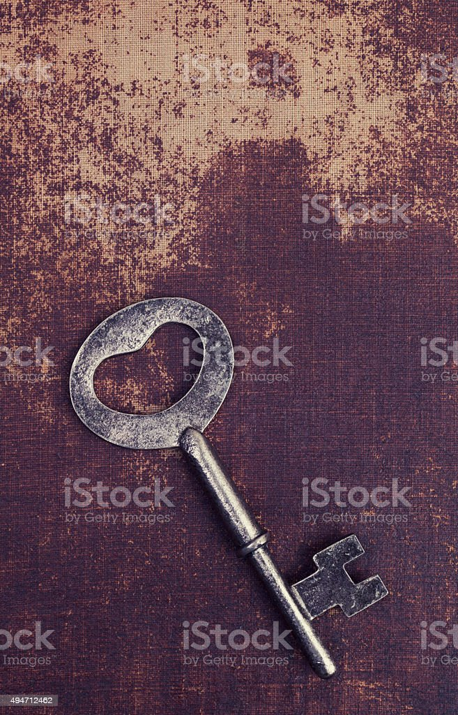 Old vintage key on a faux leather material surface stock photo