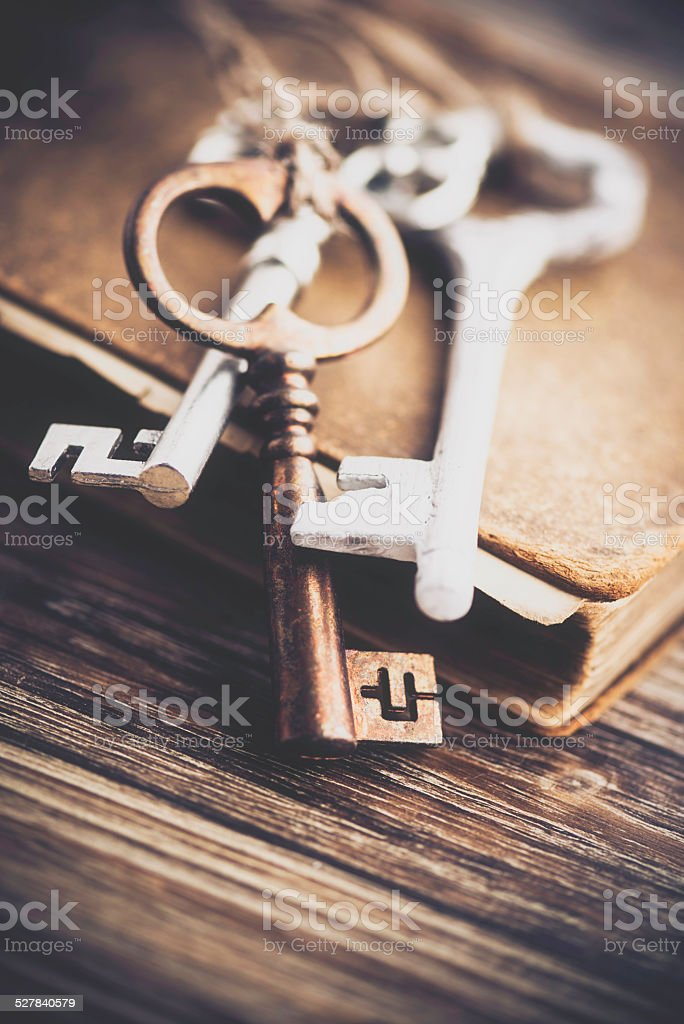 Old vintage keys on weathered old book stock photo