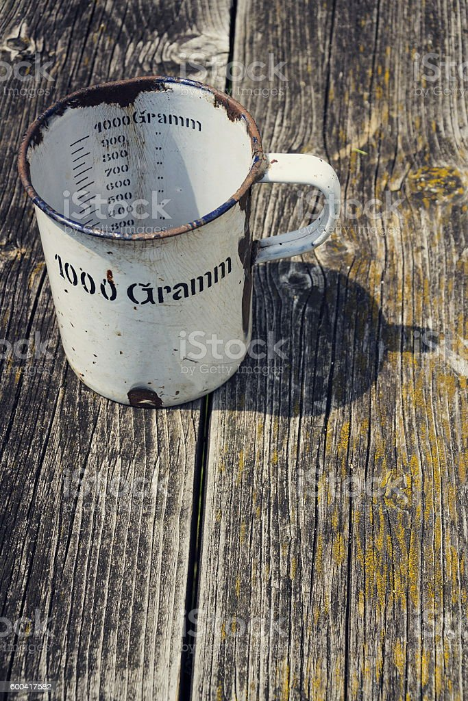 Old vintage metallic cup for 1000 grams with  wooden background stock photo