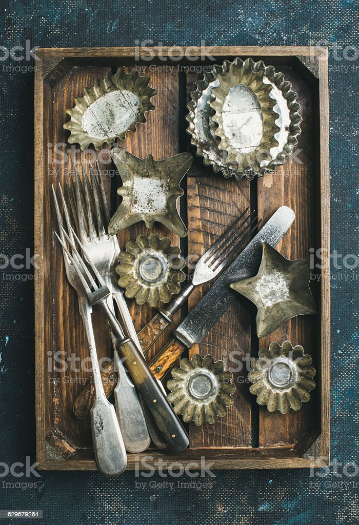 Old vintage tin baking molds and cutlery in wooden tray stock photo