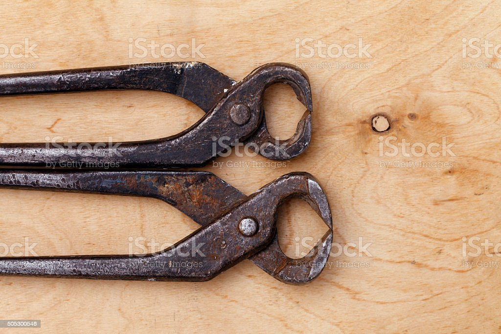 old vintage tongs tool on a wooden background stock photo