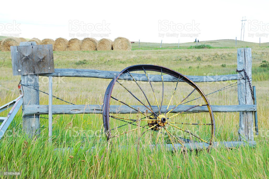 Old vintage wagon wheel leaning against a fence post. stock photo