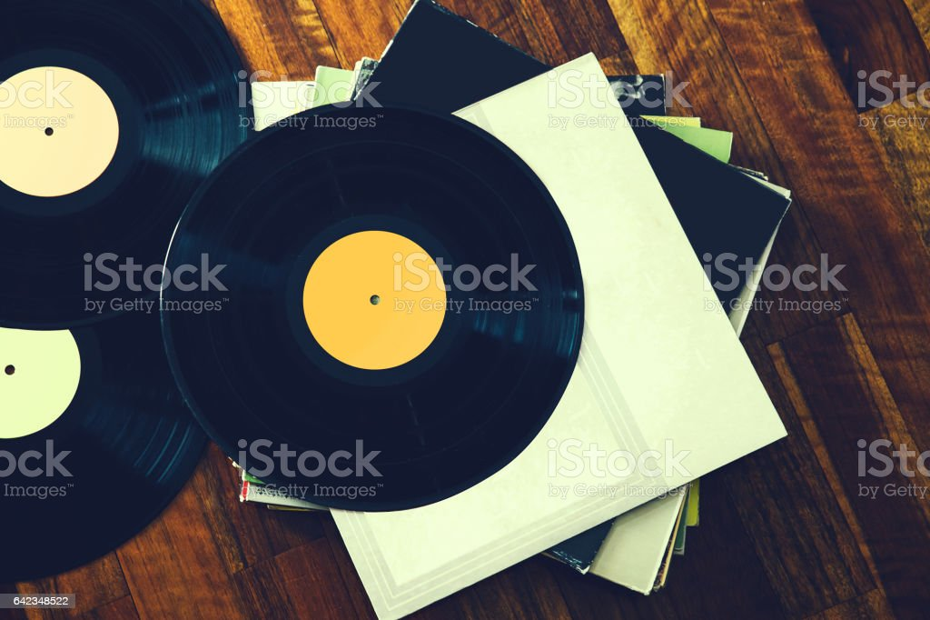 Old vinyl record and a collection of albums on wooden background. stock photo